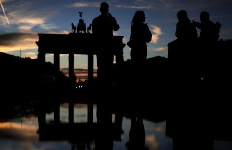 Personas caminando por delante de la puerta de Brandenburgo, en Berlín, al atardecer.