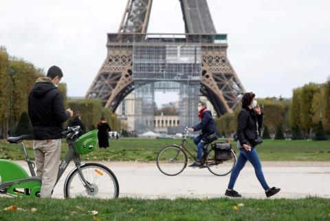 Varias personas pasean por delante de la Torre Eiffel de París