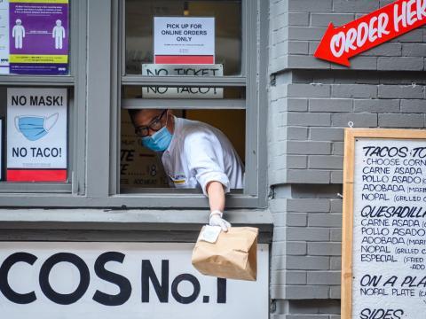 Un trabajador lleva mascarilla en la ventana de un restaurante de comida para llevar, el 8 de agosto de 2020, en la ciudad de Nueva York, Estados Unidos.