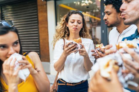 Amigos comiendo hamburguesas en la calle.