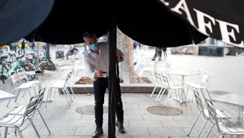 Un camarero abre una sombrilla en una terraza de Barcelona