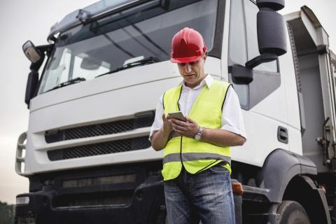 Un camionero consulta su tablet delante del camión.