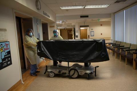 Los miembros del personal del hospital entran en el ascensor con el cuerpo de una víctima de COVID-19 en una camilla en el Centro Médico St. Jude en Fullerton, California.