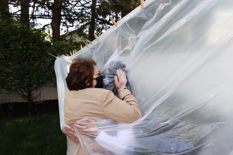 Michelle Grant abrazando a su madre a través de un trozo de plástico en Wantagh, Nueva York.