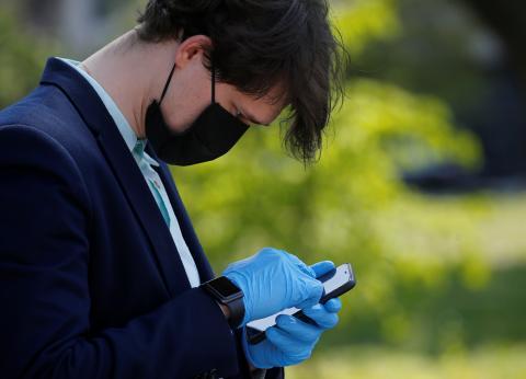 Un hombre mira un smartphone con mascarilla
