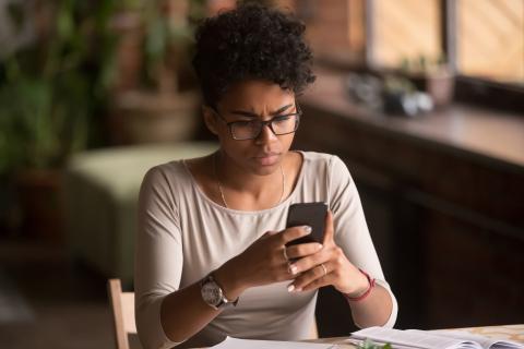 Mujer mira un mensaje extraño en su móvil.