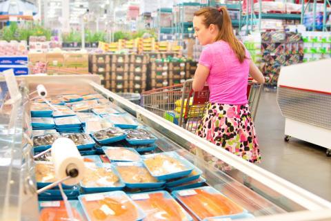 Una mujer pasa por la sección de pescados congelados del supermercado.