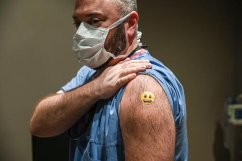 Un trabajador sanitario vacunado muestra su tirita a la prensa en el Hospital de la Universidad de Louisville, EEUU.
