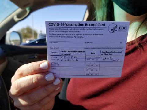 Emily Alexander, de 37 años, muestra su tarjeta de vacunación COVID-19 poco después de recibir la vacuna en State Farm Stadium en Glendale, Arizona, el 11 de enero de 2021.
