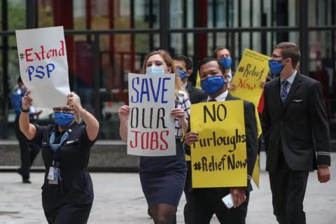 Varios trabajadores de la industria de las aerolíneas sostienen carteles durante una protesta en Federal Plaza en Chicago, Illinois, el 9 de septiembre de 2020.