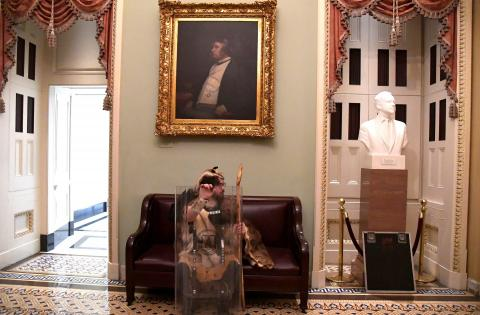 A supporter of President Donald Trump takes a seat away from the action on the second floor of the US Capitol.