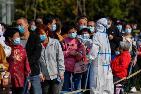 Trabajadores de la salud en China, controlan la temperatura de quienes esperan las pruebas de COVID-19.