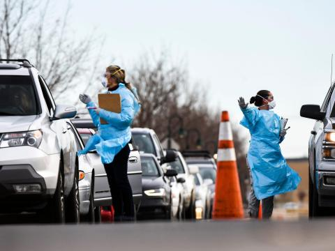Trabajadores de la salud hablando con ciudadanos que esperan las pruebas de COVID-19, 12 de marzo de 2020, Denver, Colorado, EEUU.