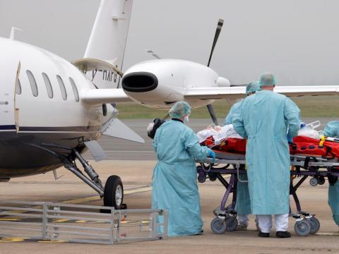 Miembros del personal médico trasladan a un paciente en el aeropuerto de Lille-Lesquin en Francia, el 10 de noviembre de 2020.