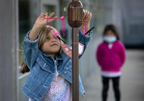 """Una niña de 5 años, Grace Truax, se quita la máscara antes de posar para una foto durante el """"día de la foto"""" en el Rogers International School, el 23 de septiembre de 2020 en Stamford, Connecticut, EEUU."""