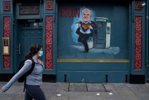 Una mujer pasea frente a una caricatura del director médico de Salud de Irlanda, Tony Holohan, en Dublín, Irlanda, el 15 de mayo de 2020.