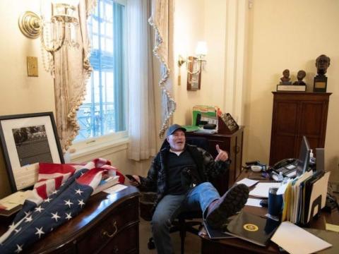 Un seguidor de Trump, sentado en la mesa de la presidenta del Congreso Nancy Pelosi.