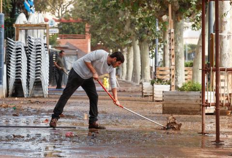 hombre limpiando agua calle, inundación