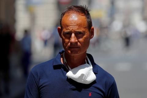 Un hombre con la mascarilla colgada del cuello