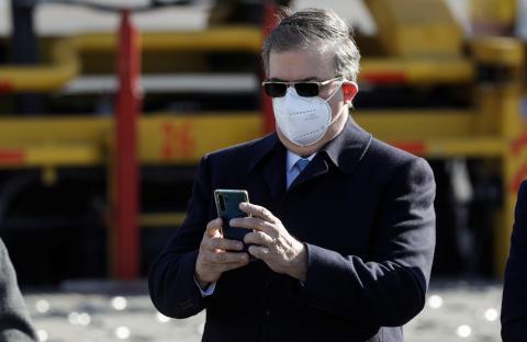 Hombre con mascarilla utiliza su teléfono