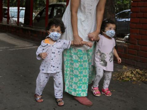 Una mujer lleva a sus niños pequeños a caminar con máscaras, en Nueva Delhi, India, el 26 de agosto de 2020.