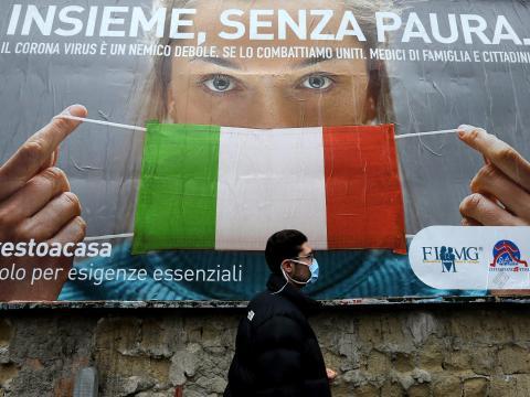 """Un hombre pasa junto a una valla publicitaria sobre el nuevo coronavirus: """"Juntos, sin miedo"""", Nápoles, Italia, 22 de marzo de 2020."""