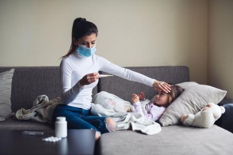 Una madre le pone el termómetro a su hija.