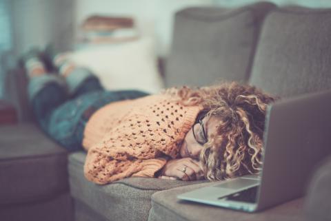 Una mujer dormida en el sofá con el ordenador delante.