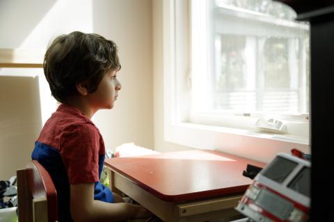 Un niño mira por la ventana sentado en una mesa de estudio.