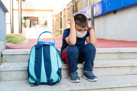 Un niño se muestra triste con la mochila al lado.
