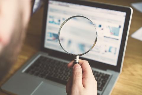 Una persona mira la pantalla de un ordenador con una lupa.