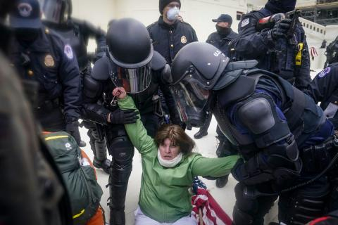 A woman is helped up by police at the Capitol in Washington.
