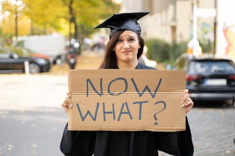"""Una recién graduada enseña un cartel en el que se lee """"¿y ahora qué?""""."""