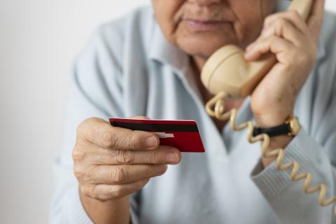 Un señor habla por teléfono con una tarjeta de crédito de la mano.
