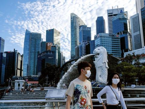 Una pareja con mascarillas camina por Singapur, 14 de marzo de 2020.