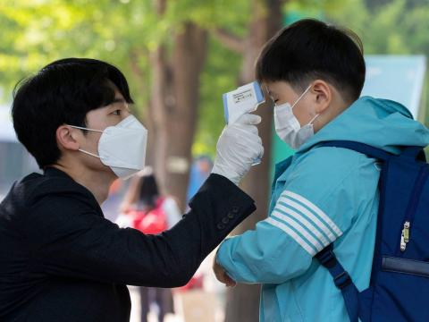Toma de temperatura al volver de clase en Seúl, 27 de mayo de 2020.