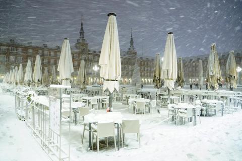 Una terraza de la Plaza Mayor de Madrid totalmente cubierta de nieve durante la noche del viernes 8 de enero.