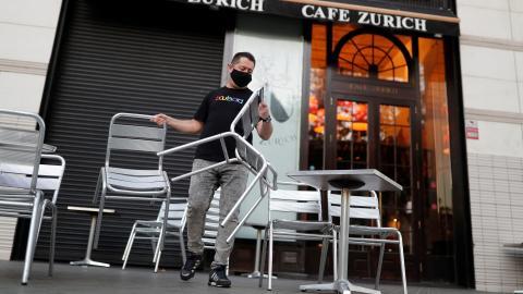 Un trabajador de una cafetería de Barcelona coloca las mesas de la terraza
