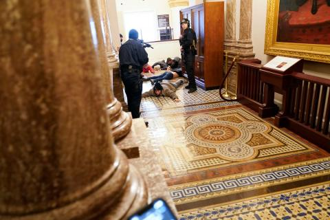 U.S. Capitol Police hold protesters at gun-point near the House Chamber.