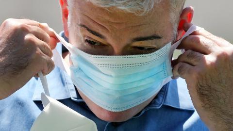 Brendan Williams, presidente de la Asociación de Atención Médica de New Hampshire, se pone una mascarilla quirúrgica encima de otra.