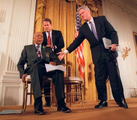 El presidente Bill Clinton y el vicepresidente Al Gore ayudan a Herman Shaw, de 94 años, sobreviviente del experimento de Tuskegee, durante una conferencia de prensa el 16 de mayo de 1997.