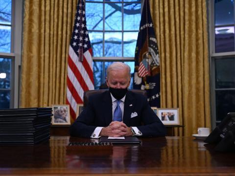 El presidente Biden se sienta frente a una bandera estadounidense y otra de sello presidencial.