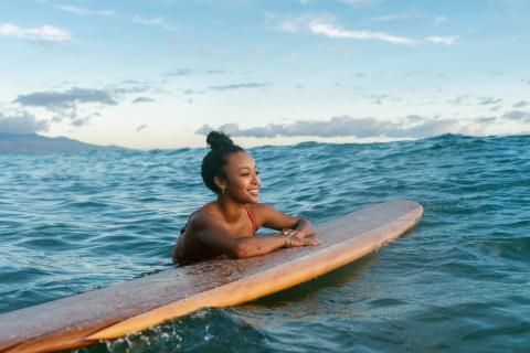 Una chica hace surf en las playas de Hawái.