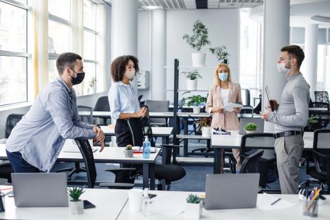Dos hombres y dos mujeres hablan en una oficina.
