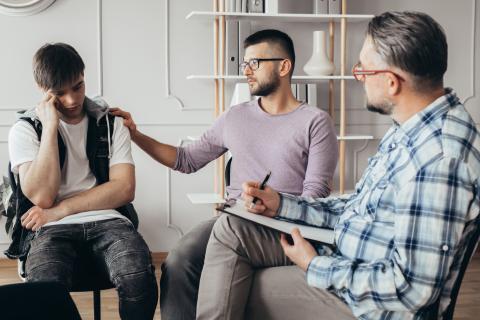 Dos hombres hablan con un adolescente.