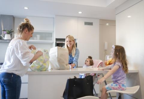 Dos madres abren bolsas delante de sus hijos.
