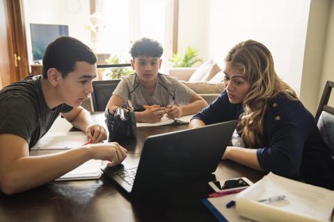 Una madre estudia con sus dos hijos.