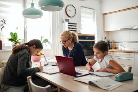 Madre que trabaja en casa con sus hijas.