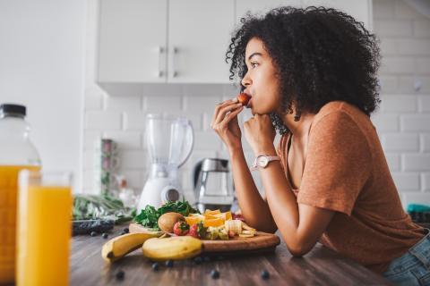 Mujer comiendo fruta.