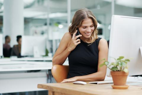 Una mujer habla por teléfono en la oficina.